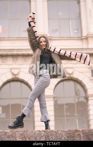 Verspielte Frau in modische Winterbekleidung, spielen mit Schal, glücklich, vor der reichen historischen Architektur, in München, Deutschland - Stockfoto