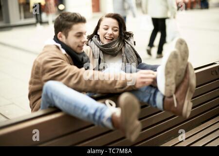 Junge Teenager Paar sitzt auf der Bank falsch herum in Stadt, heraus zusammen hängen, Beine, den Kopf, in Cottbus, Brandenburg, Deutschland - Stockfoto