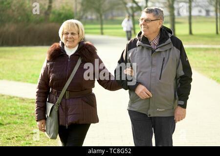 Alte senior Paar walking im Park, Arm in Arm, in Cottbus, Brandenburg, Deutschland. - Stockfoto