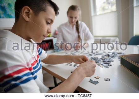 Junge Montage Puzzle am Tisch - Stockfoto