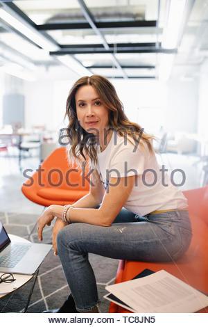 Portrait zuversichtlich Geschäftsfrau am Laptop arbeiten in Coworking Space - Stockfoto