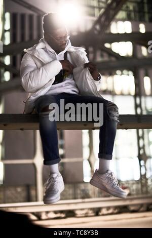 Junge afrikanische Mann sitzt auf Metall Bau der Brücke, Hackerbrücke, Hacker Brücke, in der Stadt in der Nacht, Kontrolle der Innentasche der Jacke, in - Stockfoto