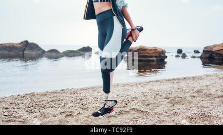 Starker Körper. Zugeschnittenes Bild der behinderten Sportler Frau in Sportswear mit Prothese tun Dehnübungen während am Strand stehen. Sport Konzept. Behinderte Sportler. Gesunder Lebensstil - Stockfoto