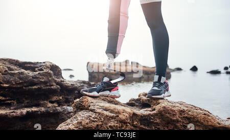 Starker Körper. Zugeschnittenes Bild der behinderte junge Frau in Sportswear mit bionischen Bein stehend auf einem Stein vor dem Meer. Behinderte Sportler. Motivation. Sport Konzept. Stockfoto