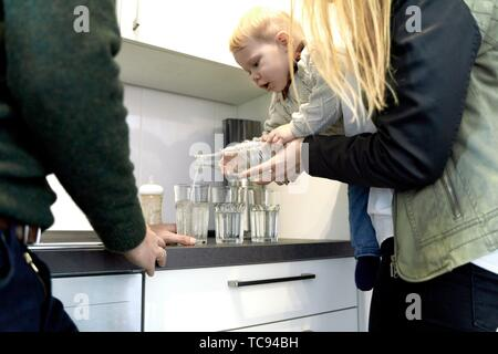 Eltern führen Baby Kleinkind Kind Wasser beim Füllen der Gläser in der Küche zu Hause, Gießen, Cottbus, Brandenburg, Deutschland. - Stockfoto
