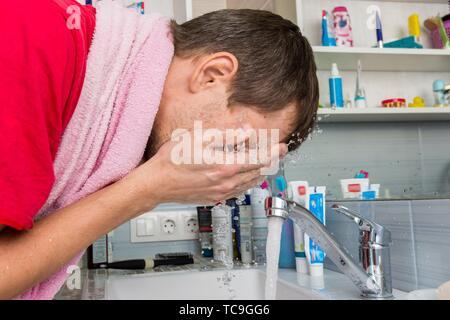 Mann sein Gesicht waschen am Morgen im Bad. - Stockfoto
