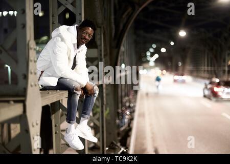 Junge Mann sitzt auf Metall Bau der Brücke Haltestelle Hackerbrücke, Hacker Brücke, in der Nacht in der Stadt, neben der Straße, in München, Deutschland - Stockfoto