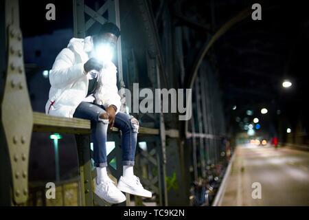 Junger Mann mit Taschenlampe von Telefon, sitzend auf Metall Bau der Brücke Haltestelle Hackerbrücke, Hacker Brücke, in der Nacht in der Stadt, neben der Straße. - Stockfoto