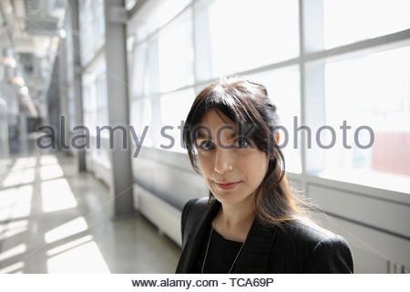 Portrait zuversichtlich Geschäftsfrau im sonnigen Büro Flur - Stockfoto