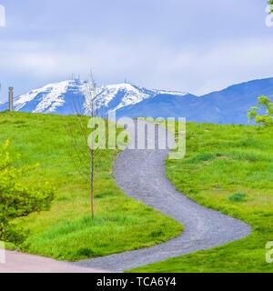 Gepflasterter Platz Bahnen auf einem Hügel mit leuchtenden grünen Gräsern bedeckt - Stockfoto