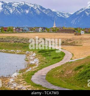 Gepflasterter Platz Weg entlang der felsigen und grasigen Ufer kurvt bei bewölktem Himmel - Stockfoto