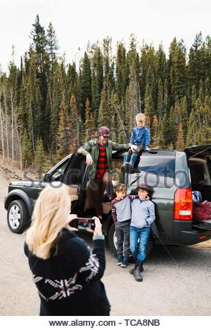 Mutter mit Kamera Handy fotografieren Familie außerhalb Auto am Straßenrand - Stockfoto