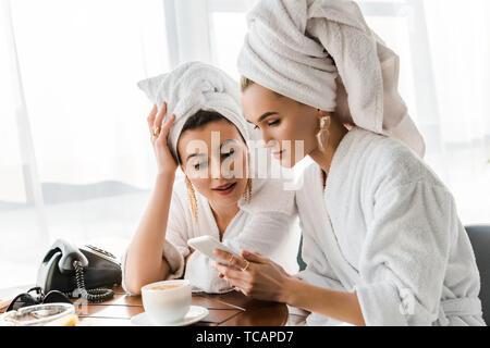 Stilvolle Frauen in Bademänteln und Schmuck mit Handtüchern auf Köpfe mit Smartphone - Stockfoto