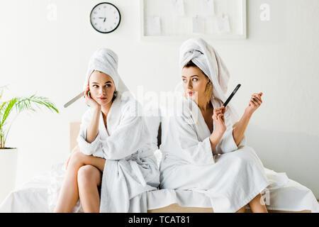 Stilvolle Frauen in Bademänteln und Schmuck, mit Handtüchern auf den Köpfen sitzen auf dem Bett mit nagelfeilen - Stockfoto