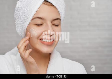 9a10c8647dc0dd ... Bademantel; Weibliches Gesicht mit Anwendung der Creme für den  Wasserhaushalt. Schöne, hübsche Frau in Weiß