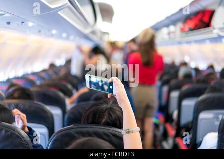 Reisende nehmen selfie Foto vom Handy im Flugzeug Sitz. Bild von der Rückseite. - Stockfoto