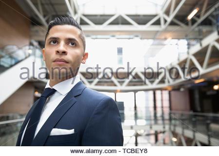 Portrait zuversichtlich, ehrgeizige junge Unternehmer auf Büro atrium Balkon - Stockfoto