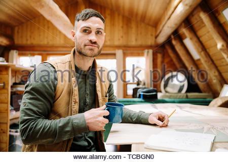 Portrait zuversichtlich männliche Künstler zeichnen und Kaffee trinken an der Kabine Tabelle - Stockfoto