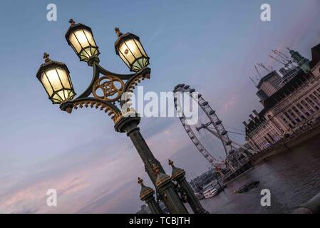 Blick auf das London Eye und die City Hall von London aus die Westminster Bridge mit einer schönen Straße Licht nach Sonnenuntergang. - Stockfoto