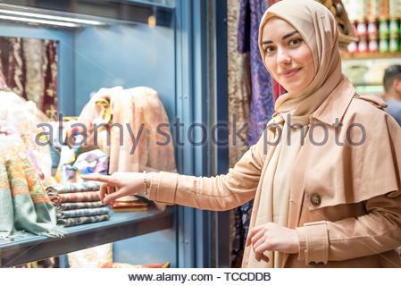 Schöne muslimische Frau in Kopftuch und modernen Kleidung sieht auf Kleidung in Ägypten Basar, Istanbul, Türkei verkauft. Moderne muslimische Frauen - Stockfoto