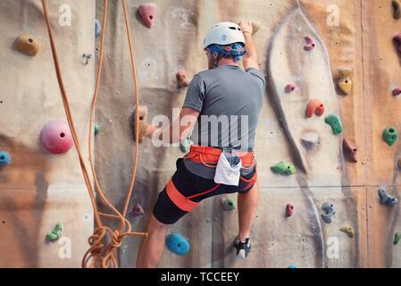 Junger Mann üben Klettern an künstlichen Wänden im Innenbereich. - Stockfoto