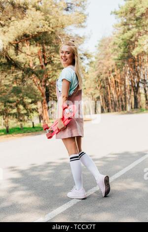 Die volle Länge der lächelnde blonde Mädchen stehen auf der Straße und der Holding penny Board - Stockfoto