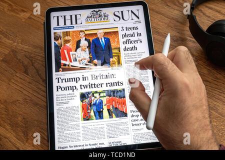 Paris, Frankreich - Jul 6, 2019: der Mensch Lesen auf Apple iPad Pro die Sonne Zeitung über Donald Trump United States presidential Besuche in Irland und das Vereinigte Königreich treffen Königin Elizabeth - Stockfoto