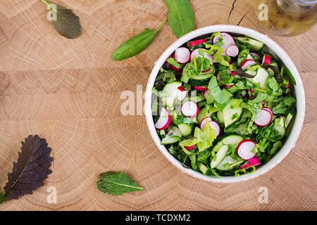 Frischer Salat aus Gurken, Radieschen und Kräutern. Flach. Ansicht von oben