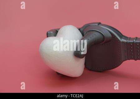 Der eiserne Arm von einem Roboter hält einen weißen Herzen. Konzept der Roboter mit Herz. Roboter in der Medizin. Rosa Hintergrund. - Stockfoto