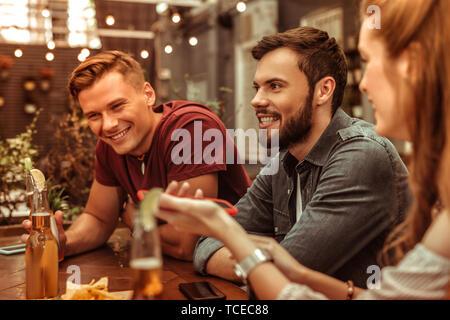 Lächelnde Menschen. Lächeln strahlend attraktiven gerne stilvolle junge Erwachsene zwei Männer an der Bar sitzen - Stockfoto
