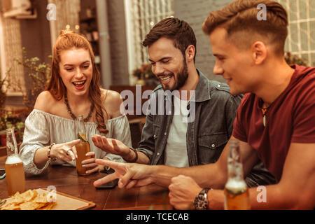 Drinks mit Freunden. Bezaubernde Rothaarige attraktive junge Dame und zwei glücklich strahlenden attraktive Jungs an der Bar mit einem Drink sitzen und Spaß haben - Stockfoto
