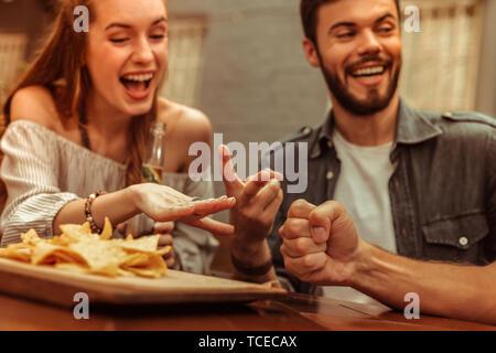 Ein Abend mit Freunden. Nahaufnahme von Lächeln strahlend leuchtende ansprechende junge erwachsene Freunde teilen ein Lachen und Spielen, während bei t Sitzen - Stockfoto