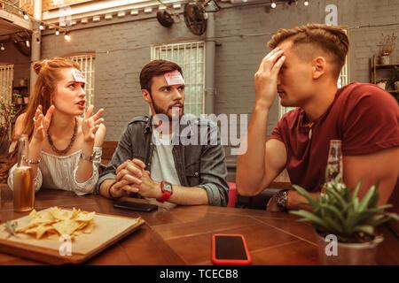 Eine hedbanz Spiel. Übertragung aktiv freudige Schön - Ansprechende attraktive strahlend leuchtende erwachsenen Freunde genießen spielen eine hedbanz Spiel an der Bar - Stockfoto
