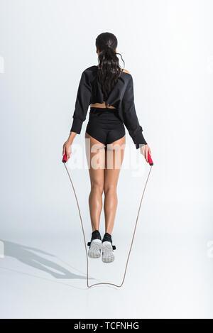 Rückansicht des sportlichen African American Girl springen mit Springseil auf Weiß - Stockfoto