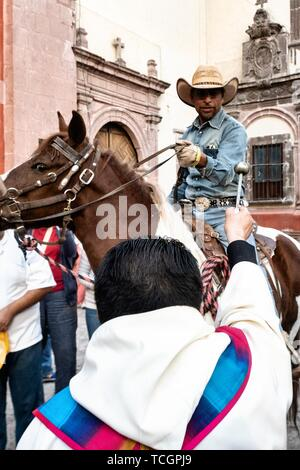 Eine römisch-katholische Priester segnet ein Cowboy mit seinem Pferd während der jährlichen Segnung der Tiere am Fest des San Antonio Abad an Oratorio de San Felipe Neri Kirche im historischen Zentrum von San Miguel de Allende, Guanajuato, Mexiko. - Stockfoto