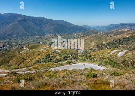 Rennradfahrer mit dem Fahrrad an der schönen gewundenen Straße unten von Cañar, Spanien, mit malerischen Blick auf die Sierra Nevada und im Süden an der Küste - Stockfoto