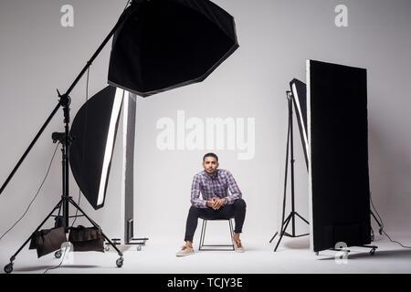 Professionelle Fotografie Studio zeigt hinter den Kulissen leuchten. Mode gutaussehenden jungen Mann Modell im Studio im Licht blinkt, saßen und - Stockfoto
