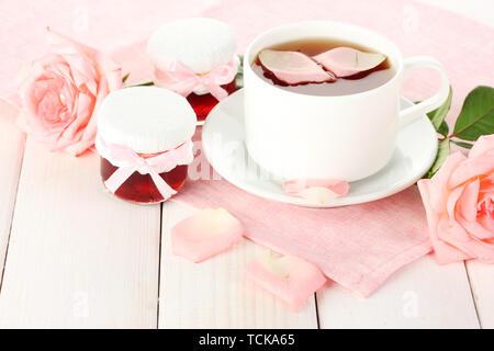 Tasse Tee mit Rosen und Marmelade auf weiße Holztisch - Stockfoto