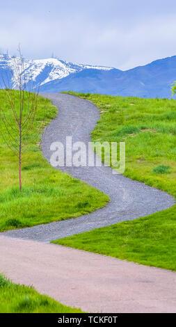 Panorama gepflasterten Wegen, auf einem Hügel mit leuchtenden grünen Gräsern bedeckt - Stockfoto