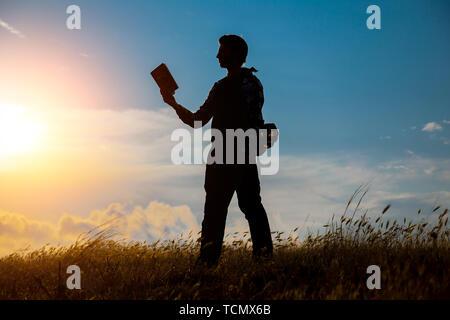 Mann lesen im Park. Silhouette der Mann sitzt auf wellenbrecher am Abend in der Nähe von Meer, liest Buch - Stockfoto