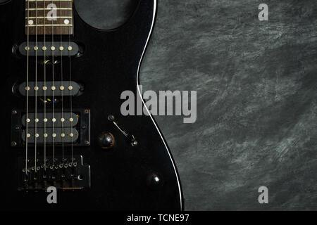 Schwarze E-Gitarre auf schwarz Zementboden. Ansicht von oben und kopieren Sie Platz für Text. Konzept der Rock Musik. - Stockfoto
