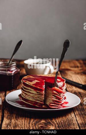 Stapel Pfannkuchen mit Beeren Obst Marmelade auf der Platte über Holz- Oberfläche - Stockfoto