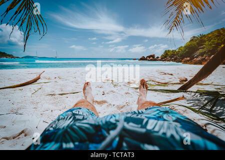 POV-shot von Mensch tragen blaue Badeshorts Festlegung auf einem schönen Sandstrand Cosos tropischen Strand Anse, La Digue, Seychellen - Stockfoto