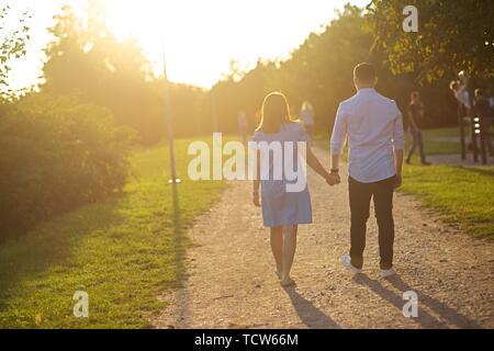Junges Paar Spaziergang durch Wiese Straße - Stockfoto