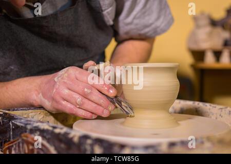 Professionelle potter Carving Becher mit Spezialwerkzeug in der Töpferei - Stockfoto