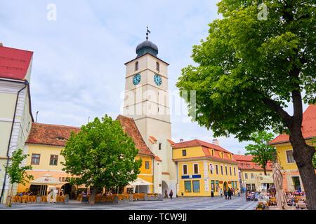Sibiu, Rumänien - 27. Mai, 2019: Der Rat Turm (Turnul Sfatului) in Hermannstadt, von den wichtigsten großen Platz gesehen, mit grünen Bäumen, an bewölkten Tag. Bevölkerung - Stockfoto