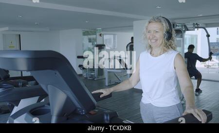 Ältere Frau ist auf einem Laufband im Fitnessstudio engagiert. blonde Frau hört Musik mit Kopfhörer auf dem Laufband - Stockfoto