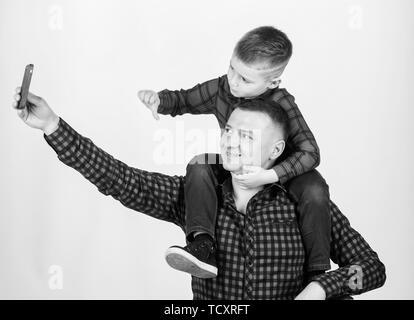 Die selfie mit Sohn. Kind reiten auf Papas Schultern. Glück, Vater des Jungen. Spaß haben. Vatertag. Vater Beispiel von edlen Menschen. Vater Sohn rote Hemden Familie Outfit. - Stockfoto