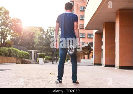 Ein Mann in Jeans und Turnschuhen auf einem hoverboard Fahrt in die Stadt. Happy Boy reiten um bei Sonnenuntergang. Moderne Elektronik für Entspannung und Unterhaltung - Stockfoto