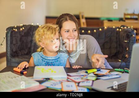 Ein Lehrer, ein Tutor für heimunterricht und ein Lehrer am Tisch. Oder Mutter und Tochter. Homeschooling